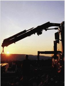 kran løfter materialer i solnedgang